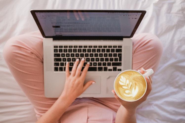 カフェラテを持ってパソコンを見る女性